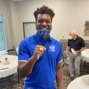 Student posing with championship ring